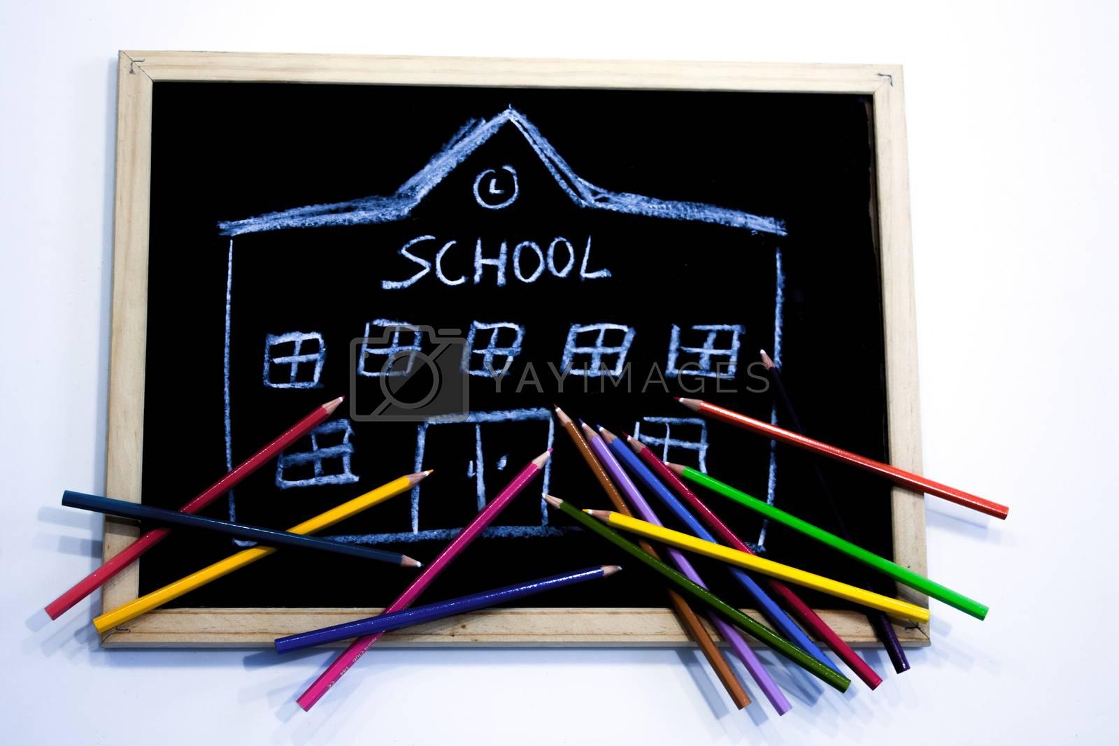 a few colored pencils arranged on a chalkboard where a school building is drawn