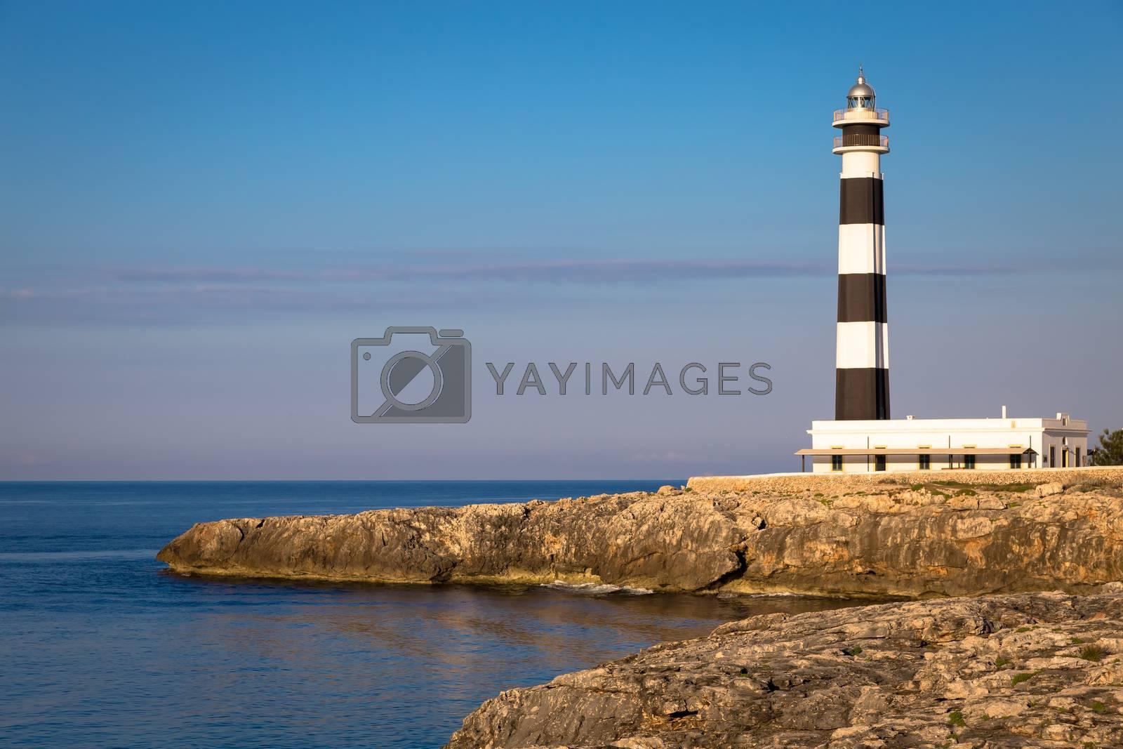 MINORCA ISLE - SPAIN - CIRCA AUGUST 2020: scenic Artrutx Lighthouse at sunset, famous landmark of the Isle