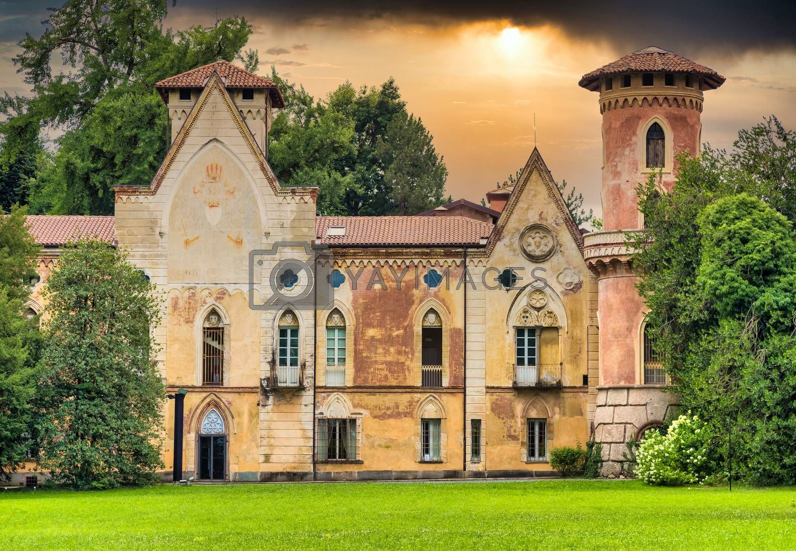 ITALY, MIRADOLO - CIRCA AUGUST 2020: gothic design castle located in an Italian garden, full of mystery, with sunset light.