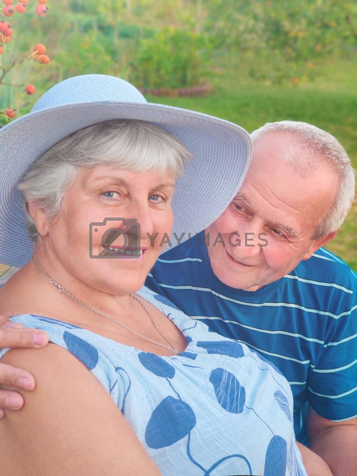 Authentic outdoor shot of aging couple having fun in the garden and blessed with love. During their game man is trying to kiss his partner and she is laughing out loud. Love and family concept. by Nickstock