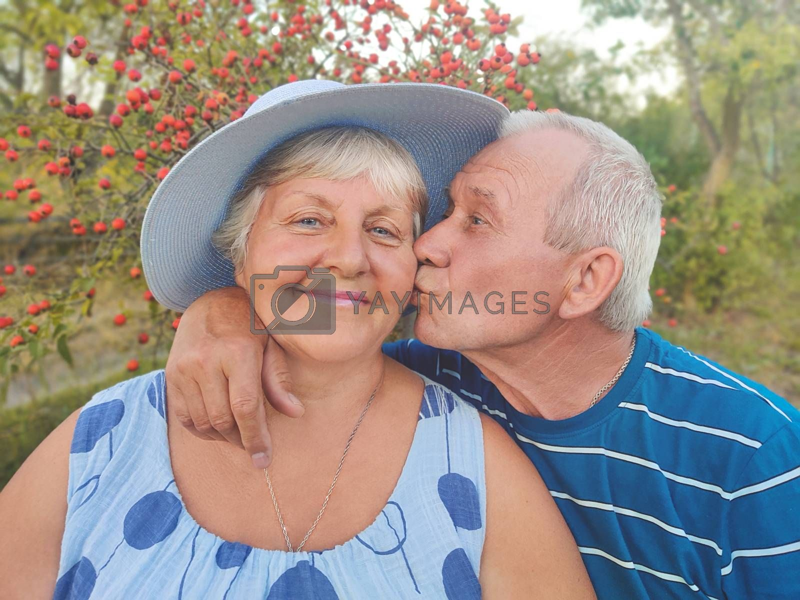Authentic outdoor shot of aging couple having fun in the garden and blessed with love. During their game man is trying to kiss his partner and she is laughing out loud. Love concept.