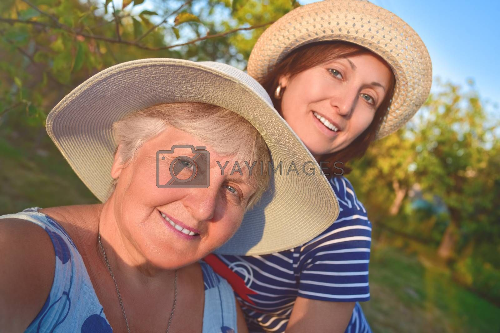 portrait of a happy elderly woman hugging her daughter and makes selfie at the park