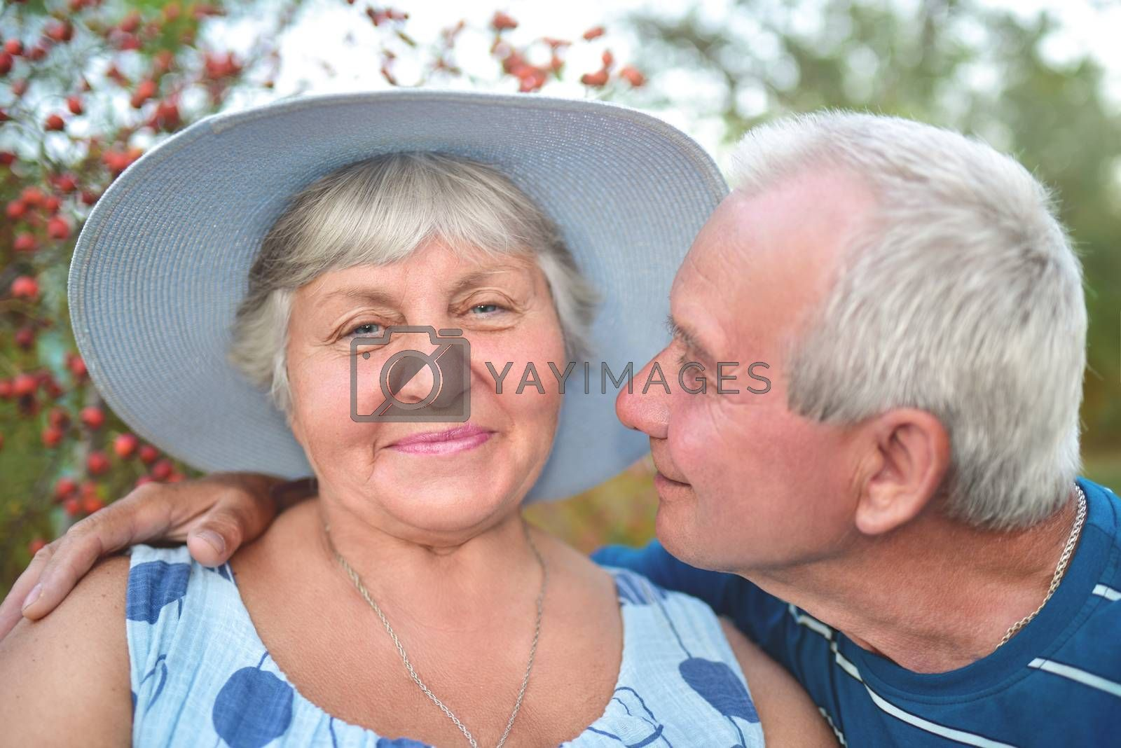 Authentic outdoor shot of aging couple having fun in the garden and blessed with love. During their game man is trying to kiss his wife and she is smiling. Love and family concept.