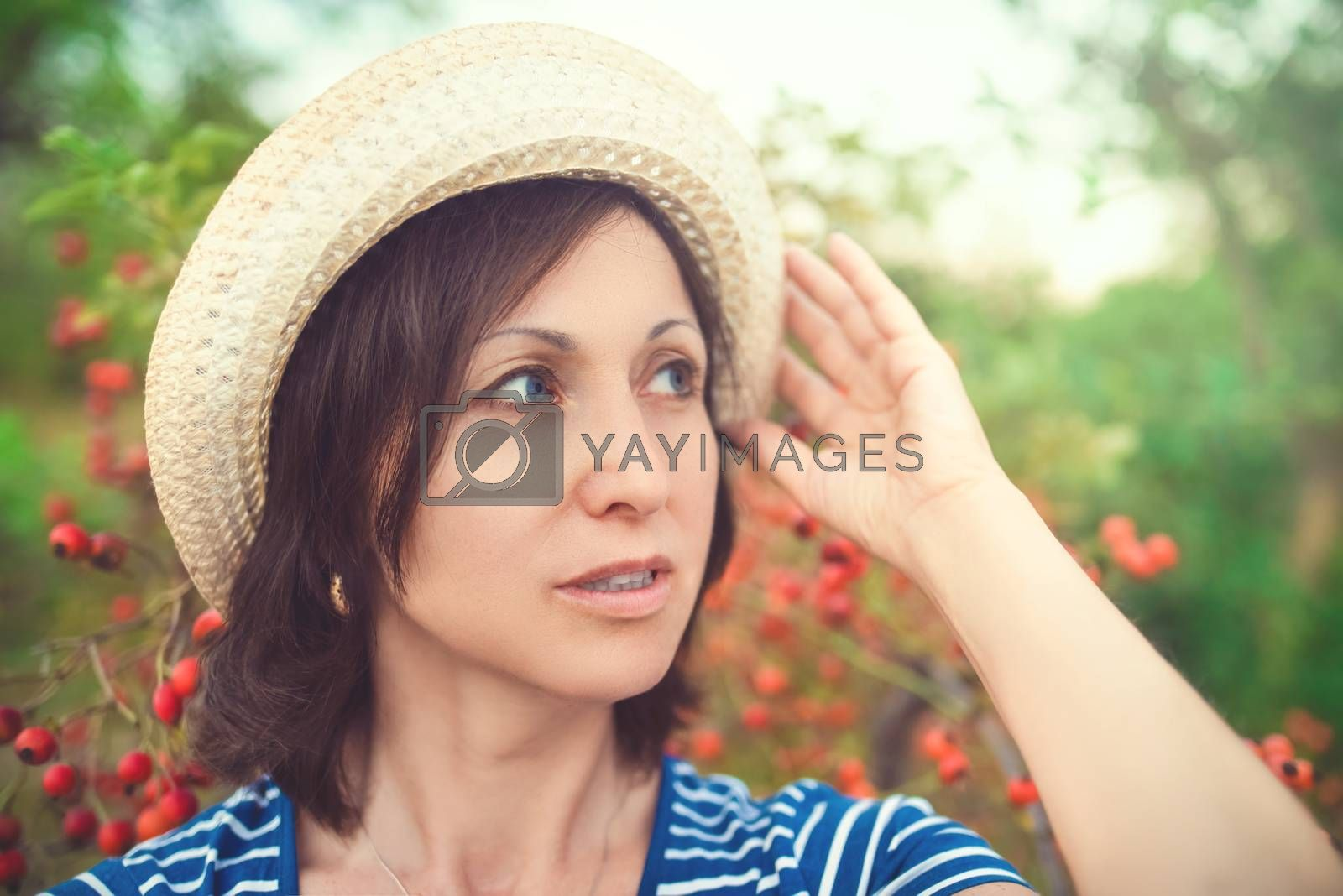 Image of beautiful middle-aged woman wearing straw hat looking aside while walking in summer park by Nickstock