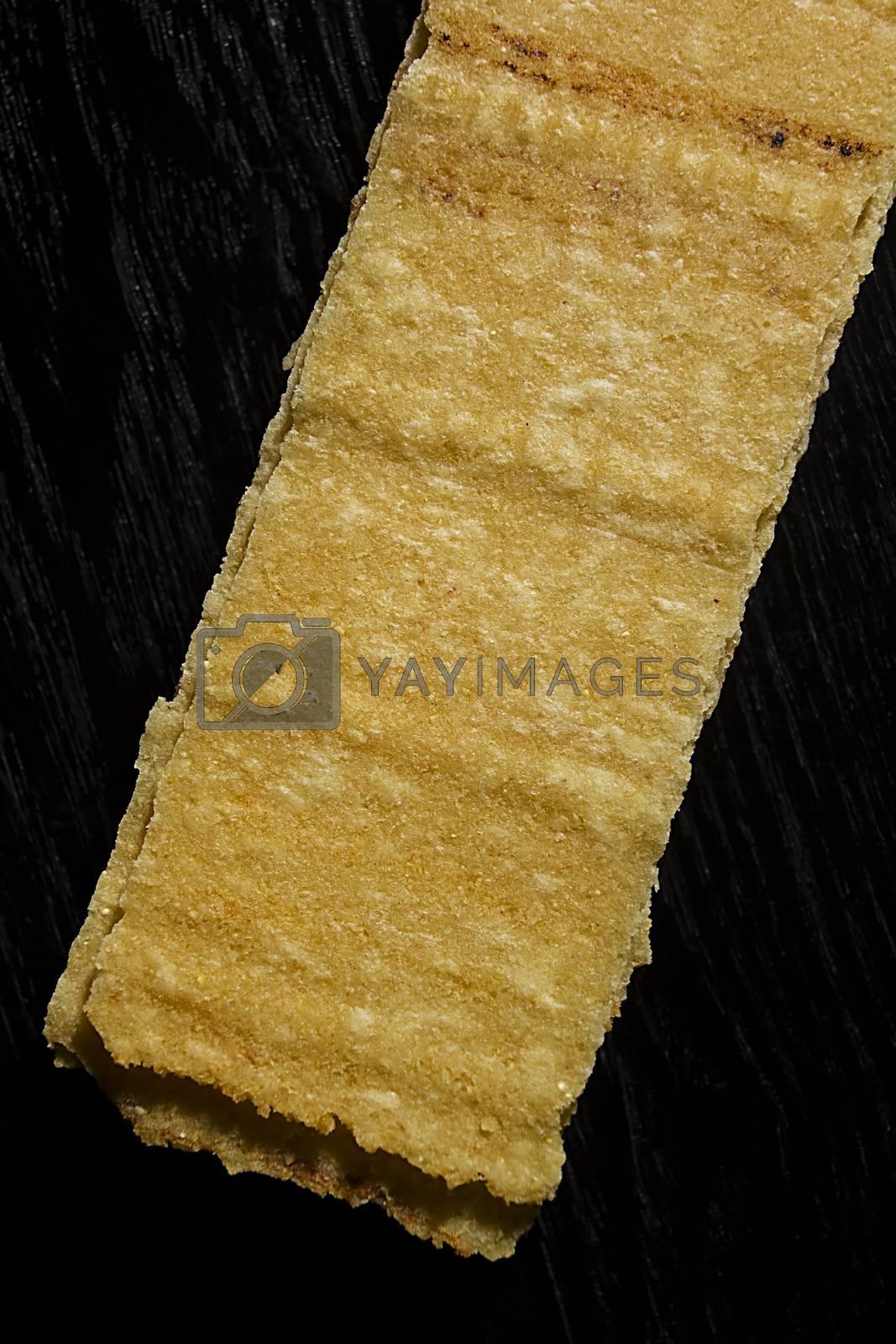Rectangular potato chips on black wooden background