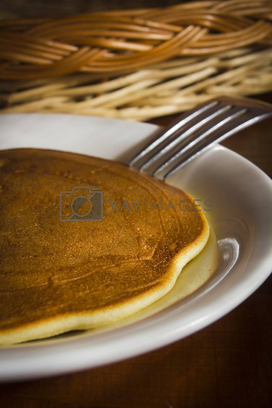 Freshly baked pancake on a plate on a wooden table