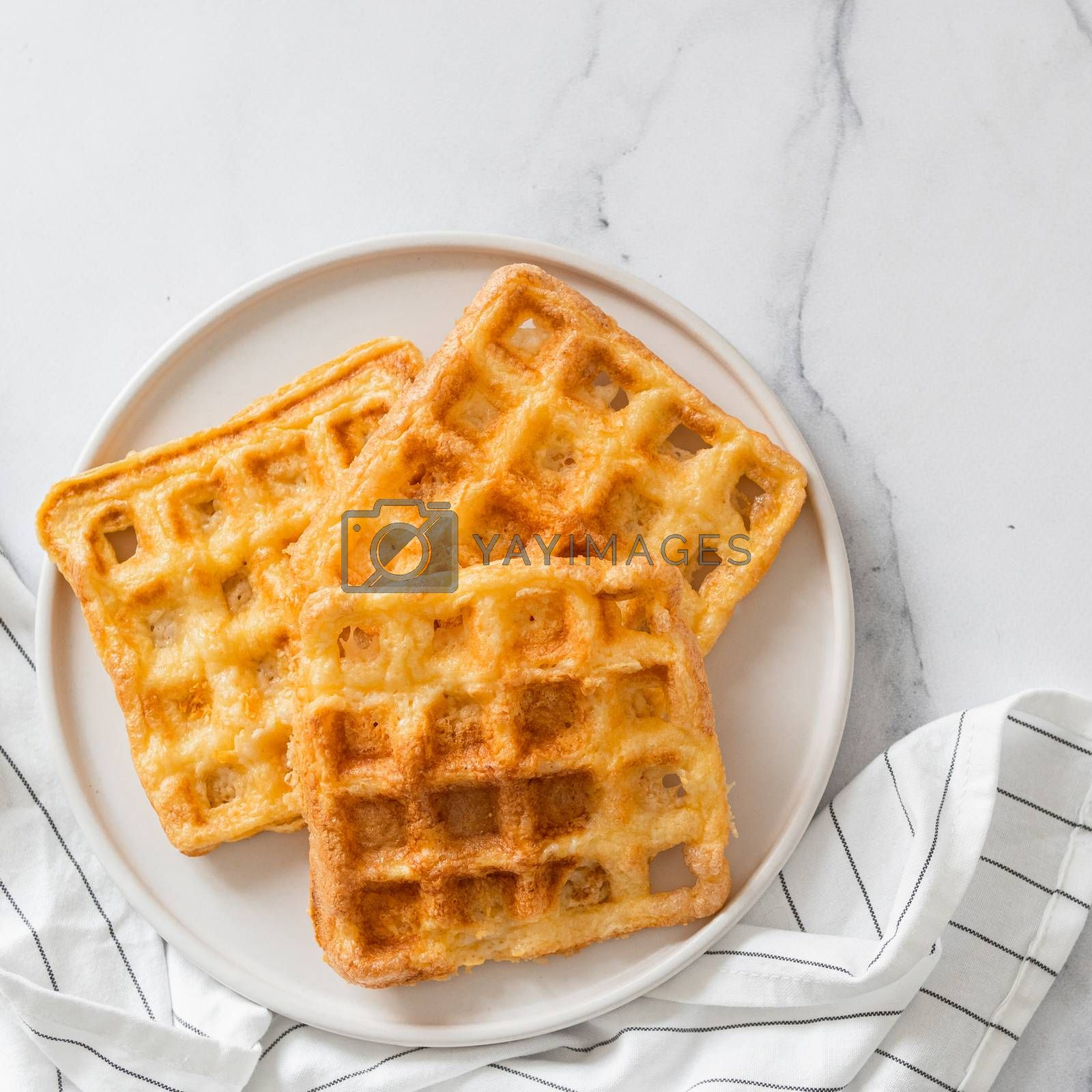 Perfect savory keto waffles. Two ingredients chaffles on plate over white marble background. Eggs and parmesan cheese low carb waffles. Top view or flat lay. Copy space for text or design.