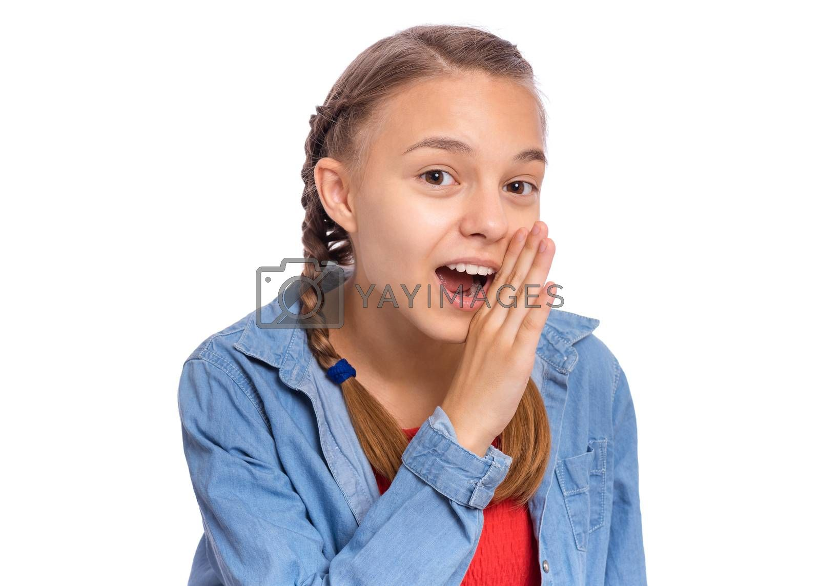 Happy teenage girl whispers, says something, covering her mouth with a palm, isolated on white background