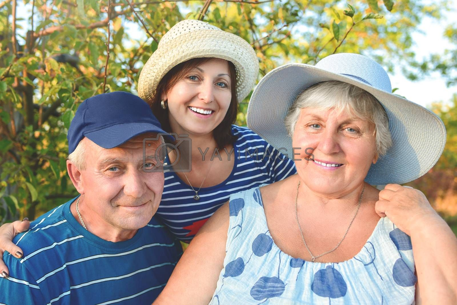 Beautiful senior couple is sitting on the bench in the park with their adult daughter. Grandma and grandpa are hugging and smiling. Real love and family relationship photo. Generations concept.