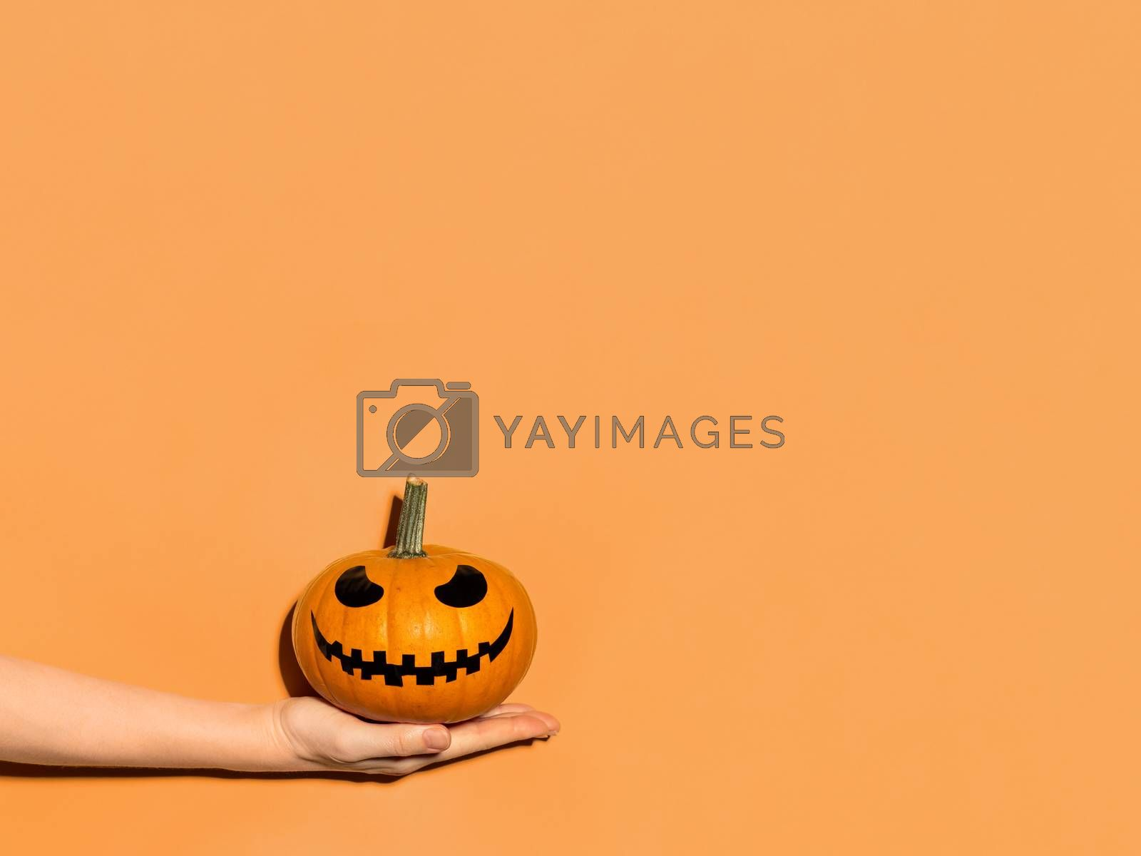 Halloween pumpkin in hand on orange background. Halloween concept with copy space for text or design. Hard light. Jack-o-lantern laughing face on orange squash