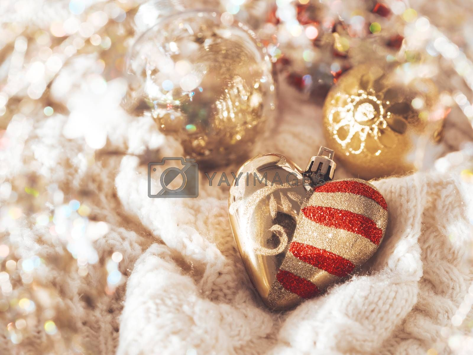 Royalty free image of Golden heart for Christmas tree on cable-knit sweater. Decorative symbol of love with red stripes and spangles. Winter holiday spirit. New year celebration. by aksenovko
