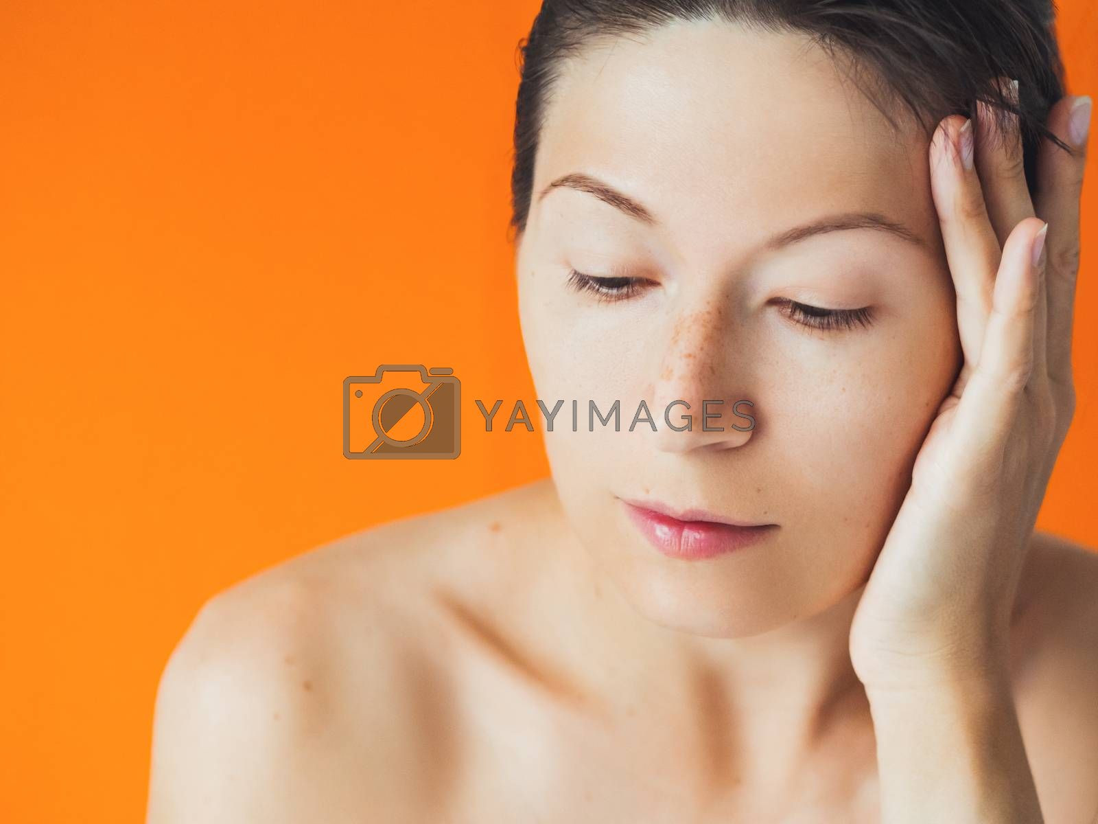 Portrait of woman with freckles on orange monochrome background. No make up. Natural beauty on bright and colorful backdrop. Banner with copy space.