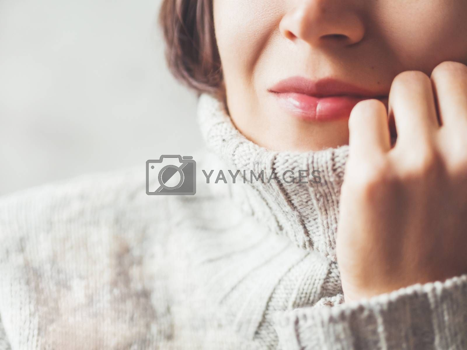 Royalty free image of Close up portrait of woman snuggling in warm grey sweater. Casua by aksenovko