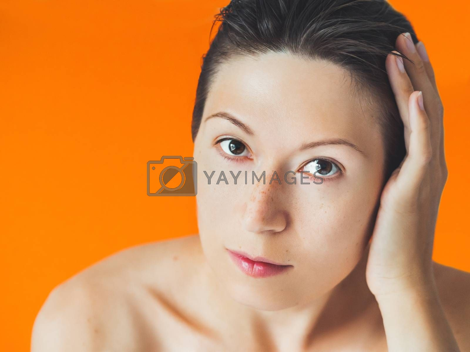 Royalty free image of Portrait of woman with freckles on orange monochrome background. by aksenovko