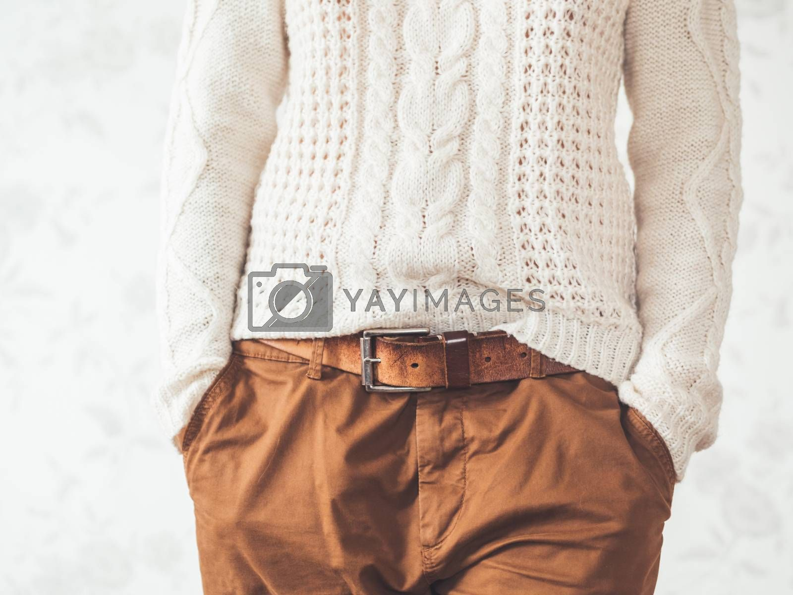 Royalty free image of Woman in cable-knit white sweater with Scandinavian pattern and brown chinos trousers with leather belt. Casual clothes for snuggle weather. Modern urban fashion. by aksenovko