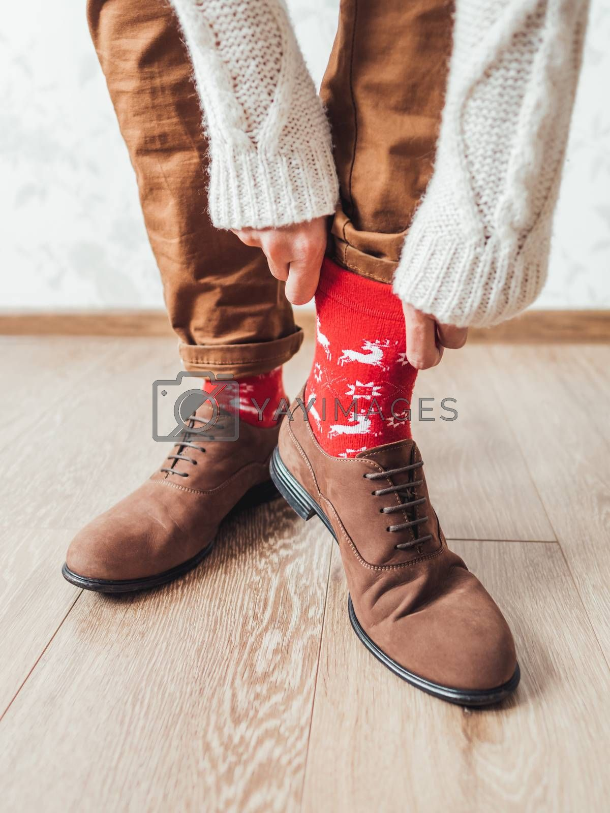 Royalty free image of Young man pulls up leg of his chinos trousers to show bright red by aksenovko