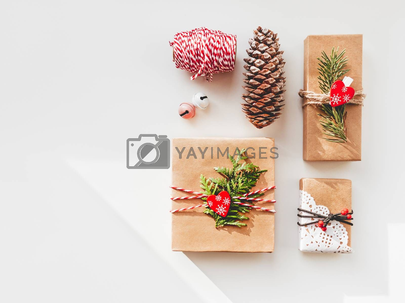 Royalty free image of Christmas DIY presents wrapped in craft paper with fir tree twigs and red hearts. Top view on decorations on New Year gifts. Festive background. Winter holiday spirit. Banner with copy space. by aksenovko