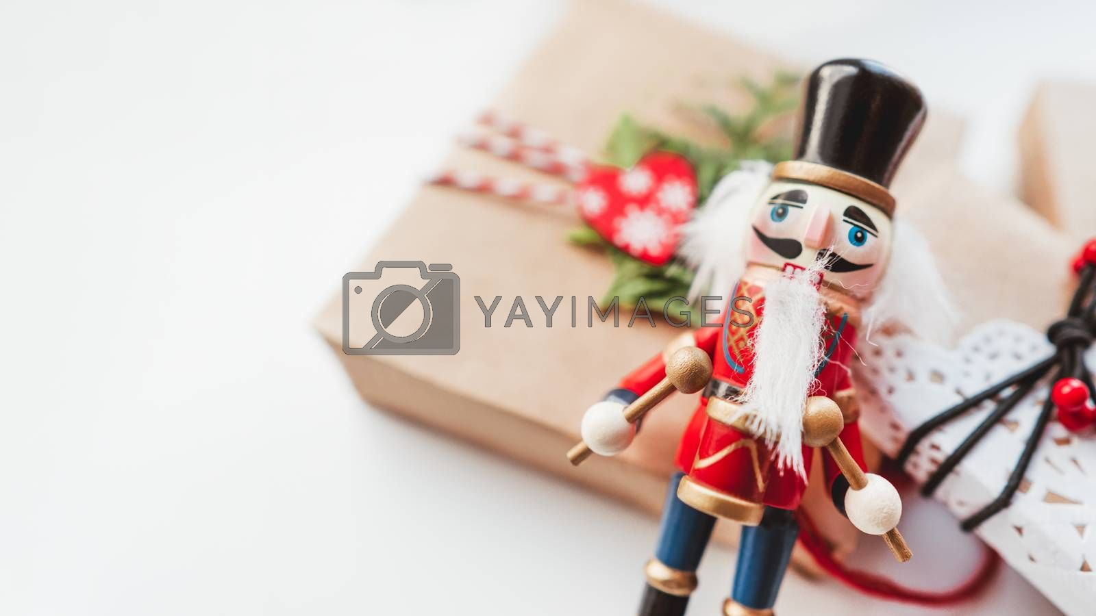 Christmas DIY presents wrapped in craft paper and wooden Nutcracker toy. Decorations on New Year gifts. Festive background. Winter holiday spirit. White background with copy space. by aksenovko
