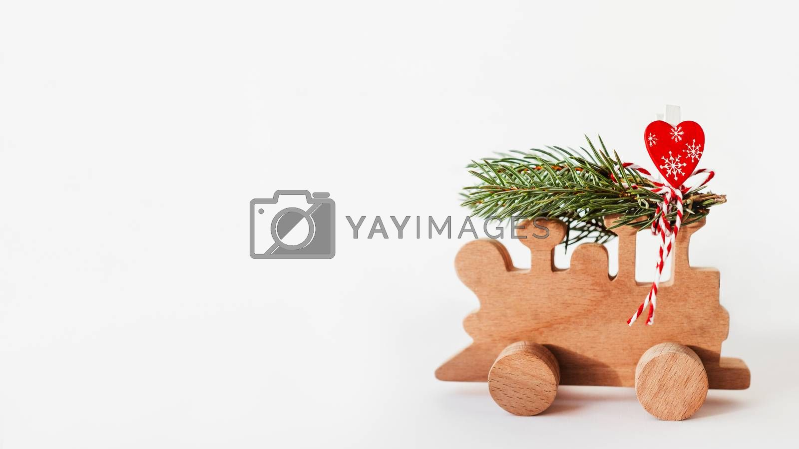 Wooden train with tied fir tree branches and red heart decoration. Cute symbol of Christmas tree brought home for New Year celebration. Winter holiday spirit. Copy space on white background. by aksenovko