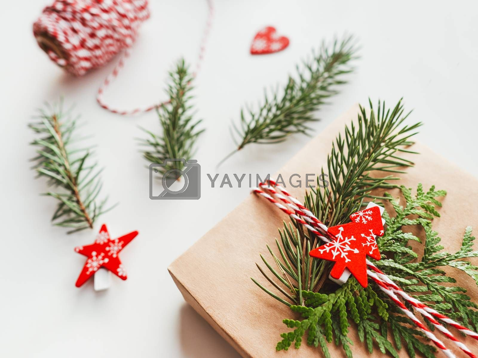 Royalty free image of Christmas DIY presents wrapped in craft paper with fir tree branches. Red decorations in shape of Christmas tree. New Year gifts. Festive background. Winter holiday spirit. by aksenovko