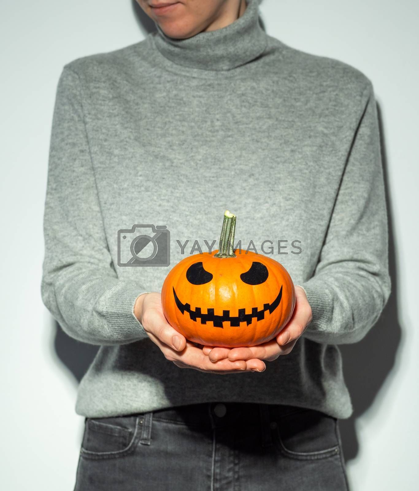 Crop unrecognizable woman holding halloween scary face bright orange pumpkin. Young woman in gray cashmere sweater and black jeans with jack-o-lantern pumpkin in hands. Snapshot style.. Copy space