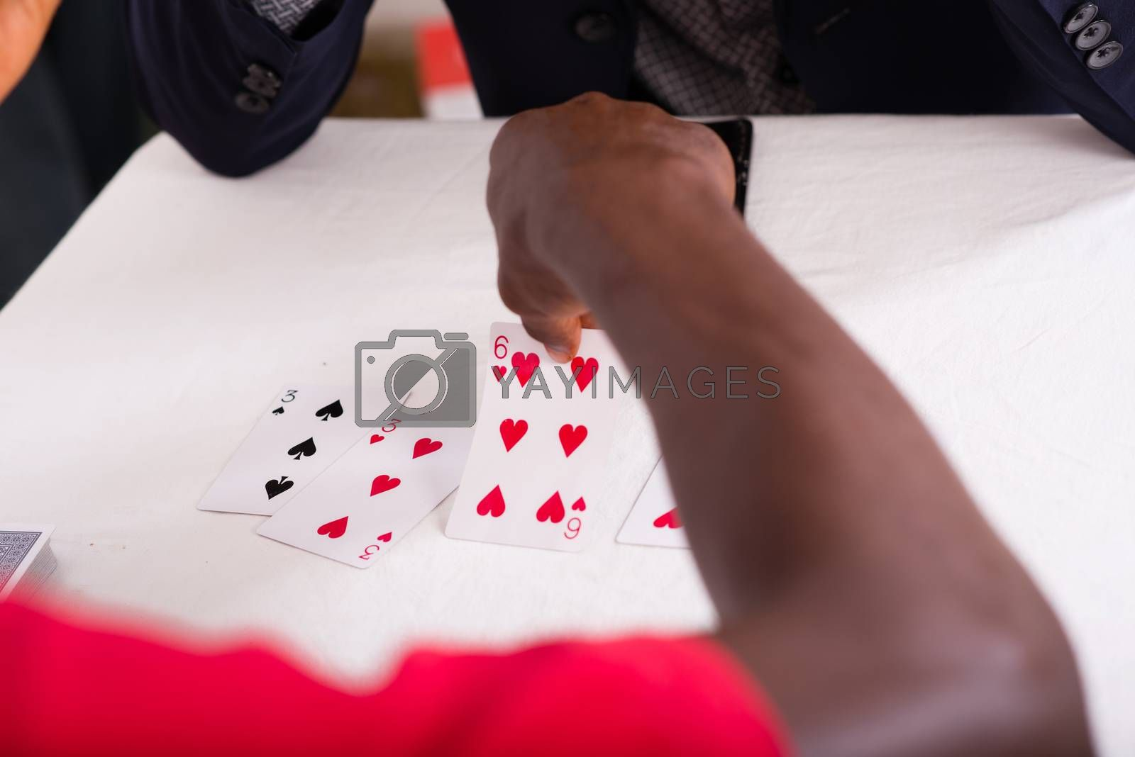 Close-up of the hands of a man holding cards and arranging them in order on the table facing his invisible opponent.