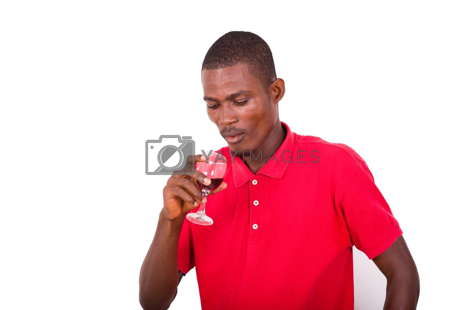 portrait of young man holding a glass of red wine and looking at it isolated on white background.