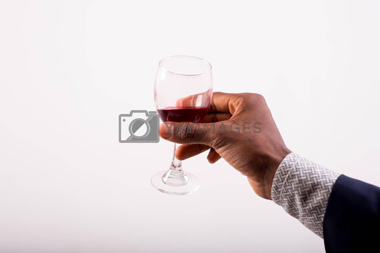 Glasses of red wine in their hand of a man in a suit. The concept of celebration and celebration.