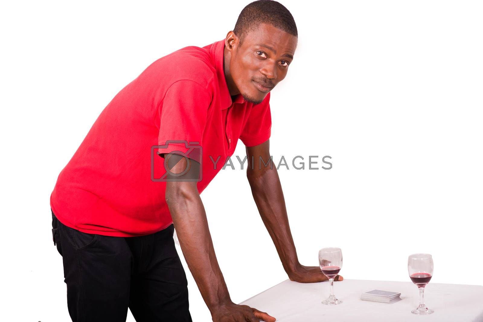 businessman leaning alone against a table with two glasses of wine in front of him and playing cards on the table.