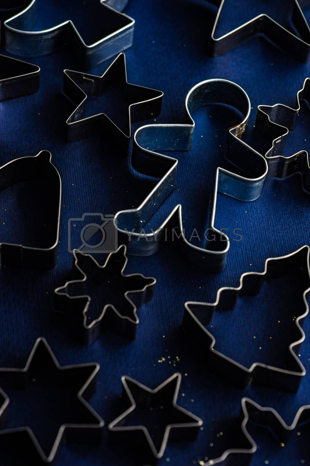 Christmas flat lay made with cookies cutters on deep blue background