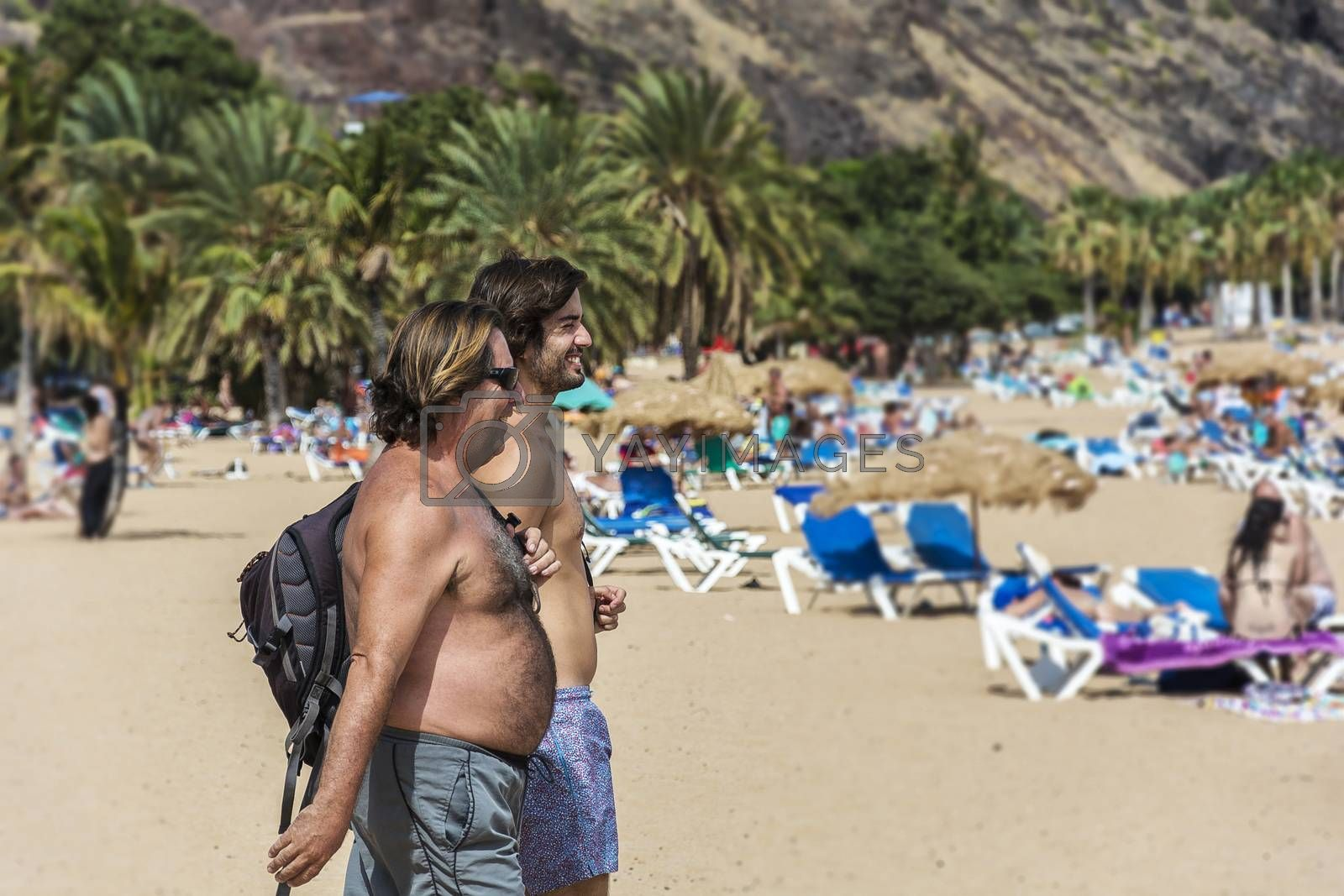 Royalty free image of Two men go to the beach to swim and sunbathe (Tenerife, Spain) by Grommik