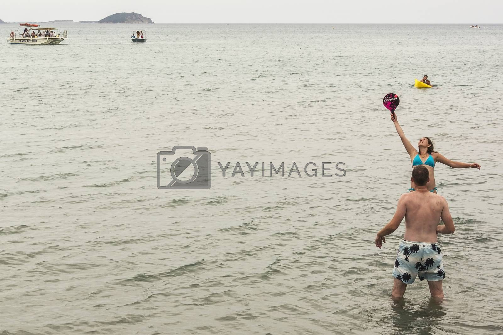 Royalty free image of Young woman and young man playing games standing in water by Grommik