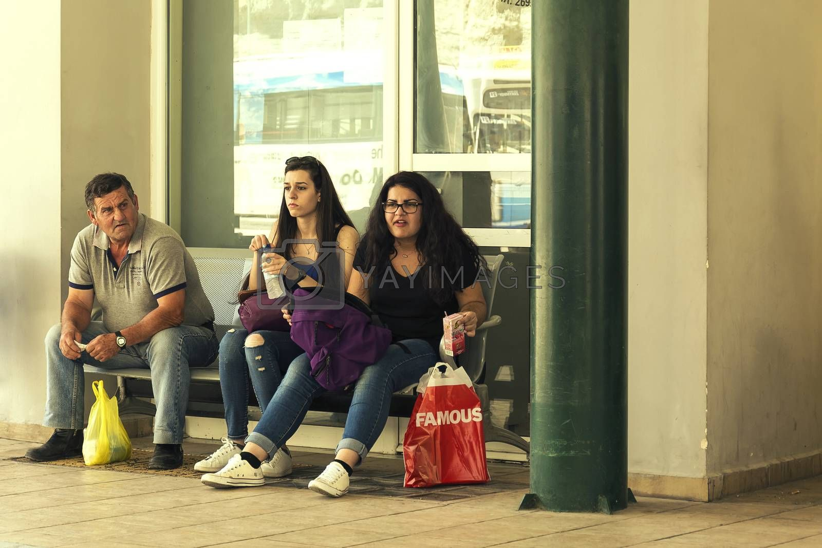 Royalty free image of Two young girls and an elderly man sit on a bench waiting for a by Grommik