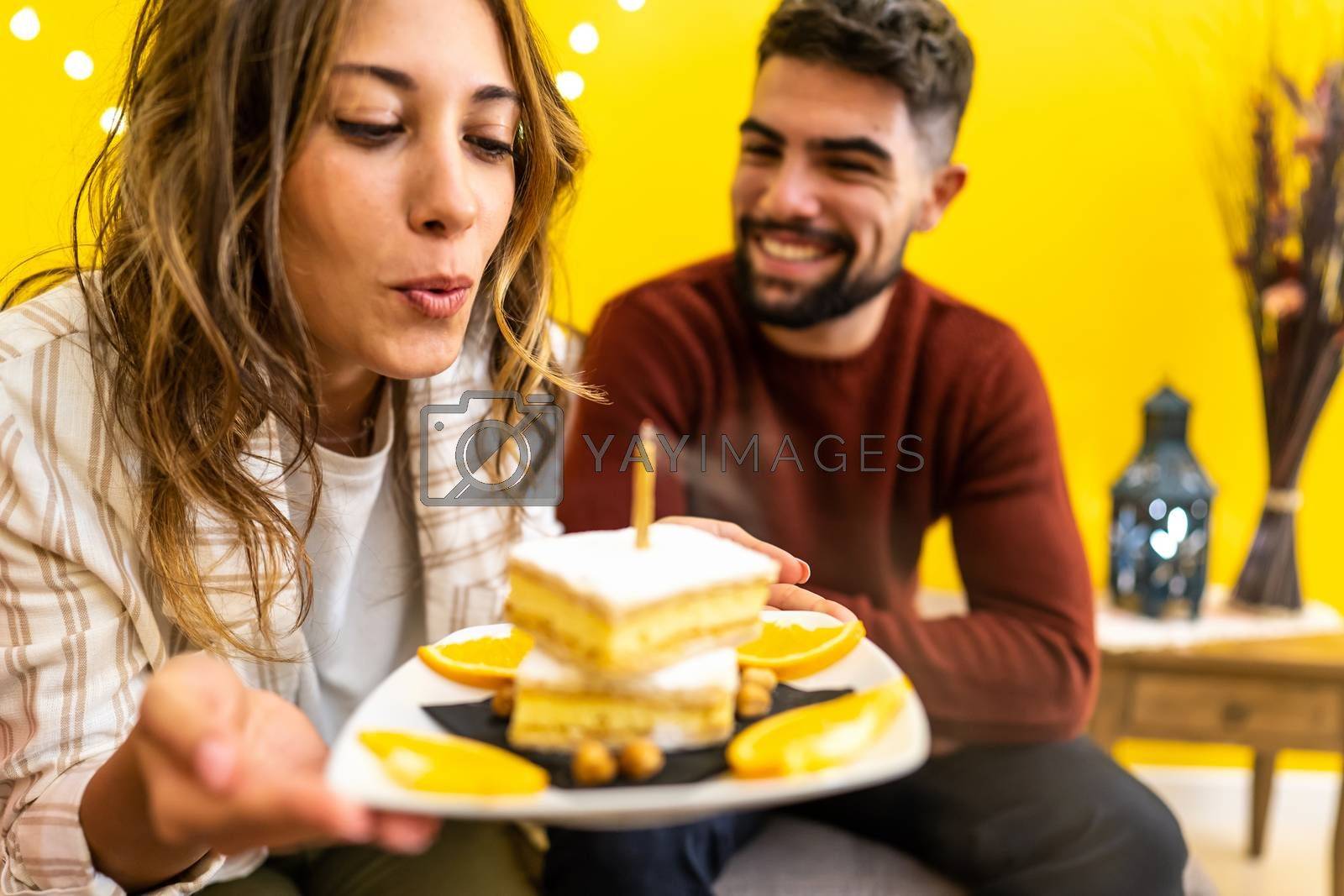 Young cute blonde woman blows out the candle of her birthday cake with her smiling boyfriend sitting on the sofa - Couple event celebration at home - Focus on the tuft of hair in the center