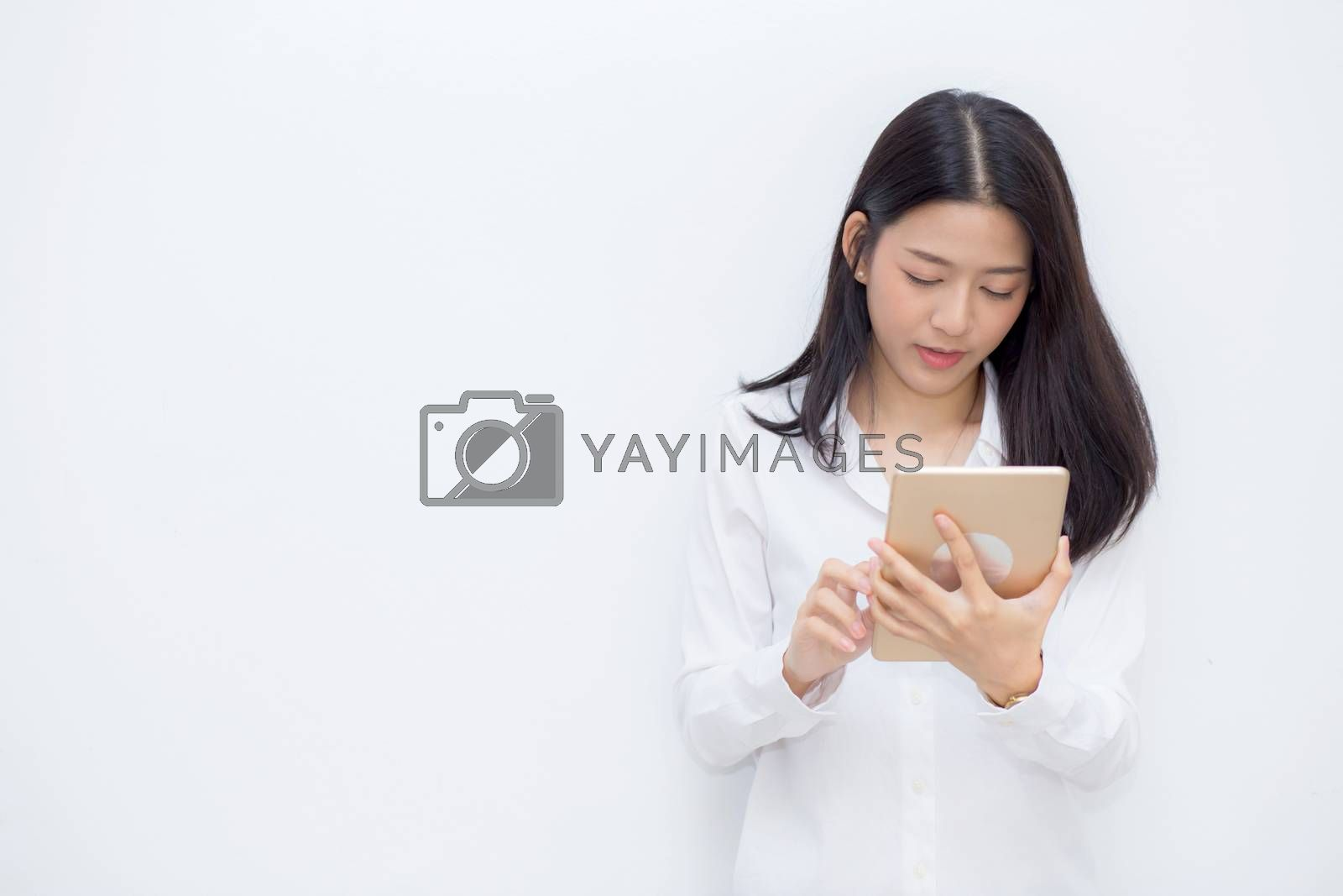 Beautiful portrait young asian woman using tablet computer cement background, businesswoman sitting looking tablet, communication concept.