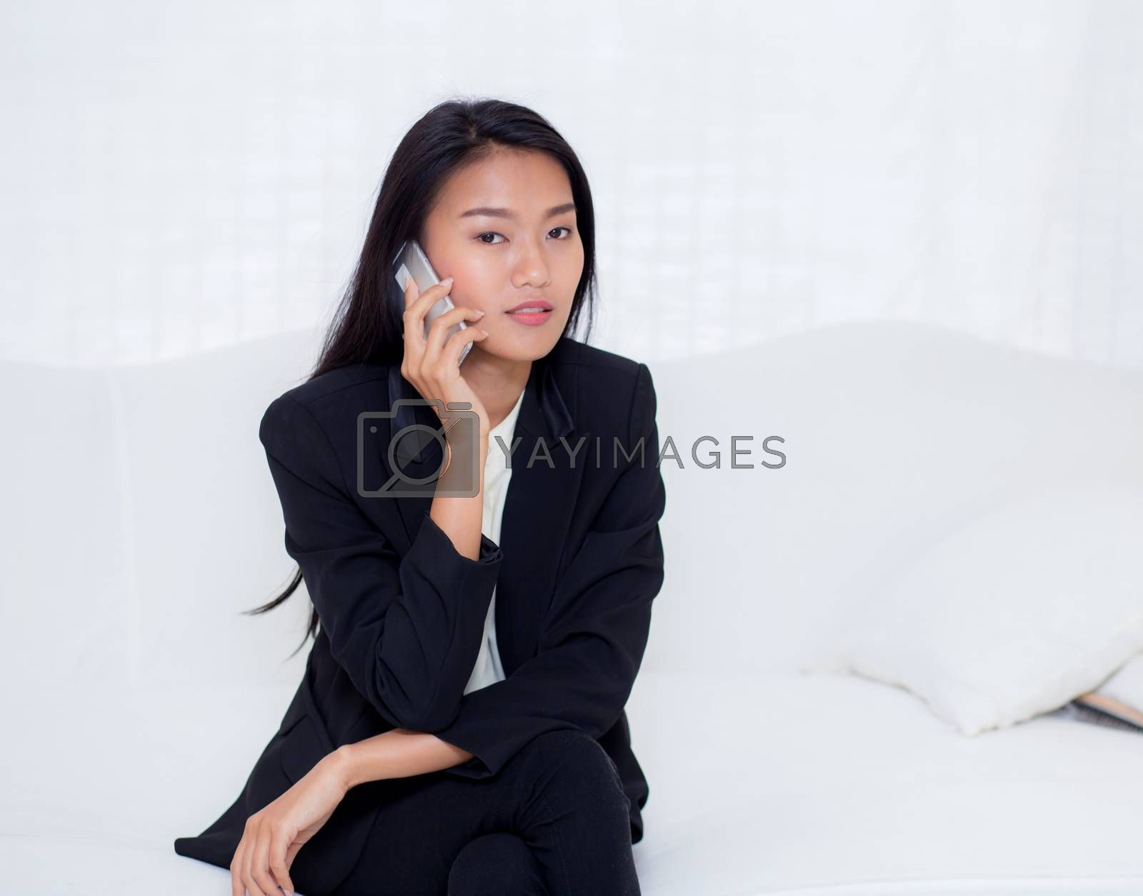 Beautiful young asian woman talking phone and smile in the living room, businesswoman sitting on sofa,businesswoman calling telephone, communication concept.