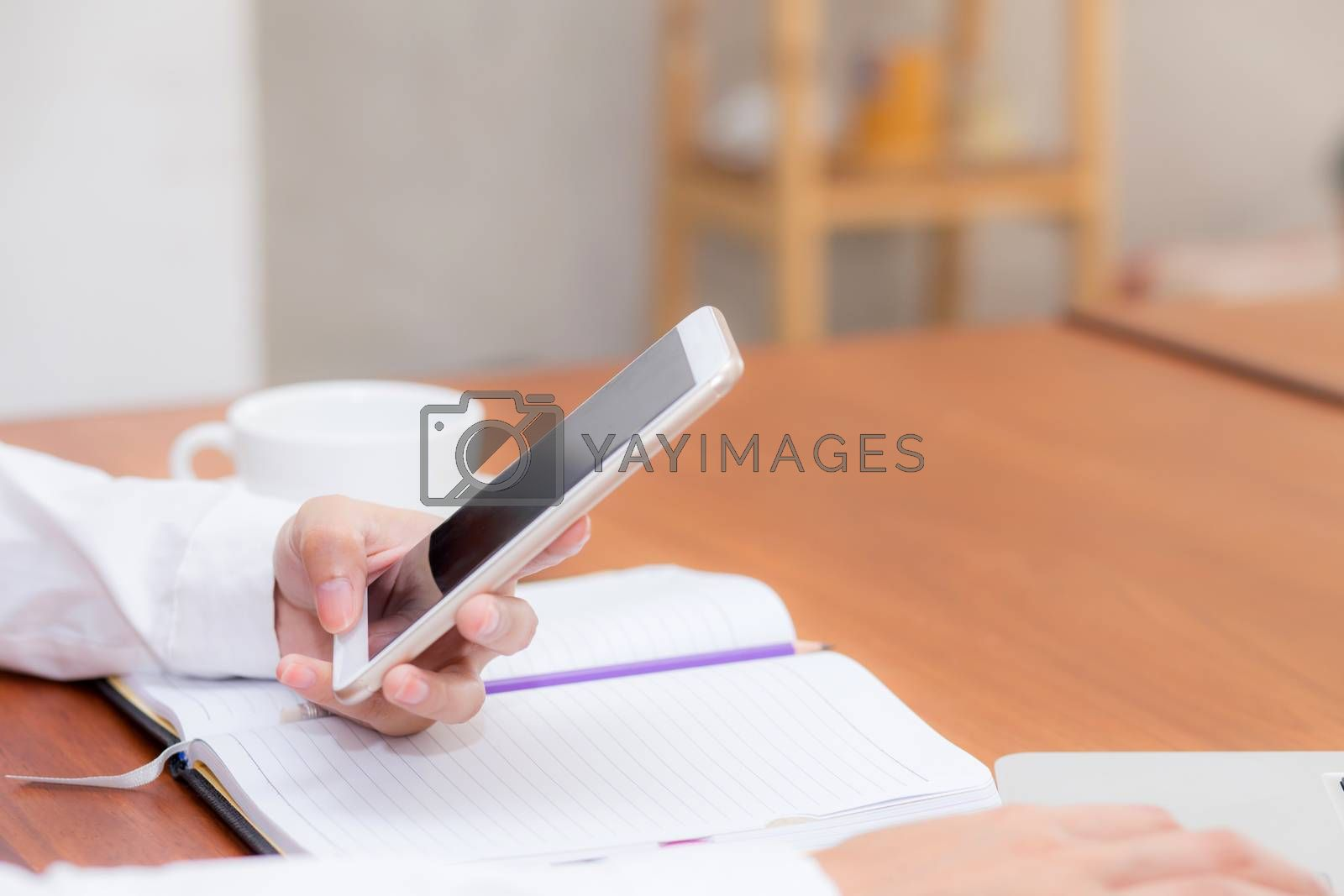 Closeup woman hand with mobile smart phone and notebook at coffee shop, girl working at cafe, communication business concept.