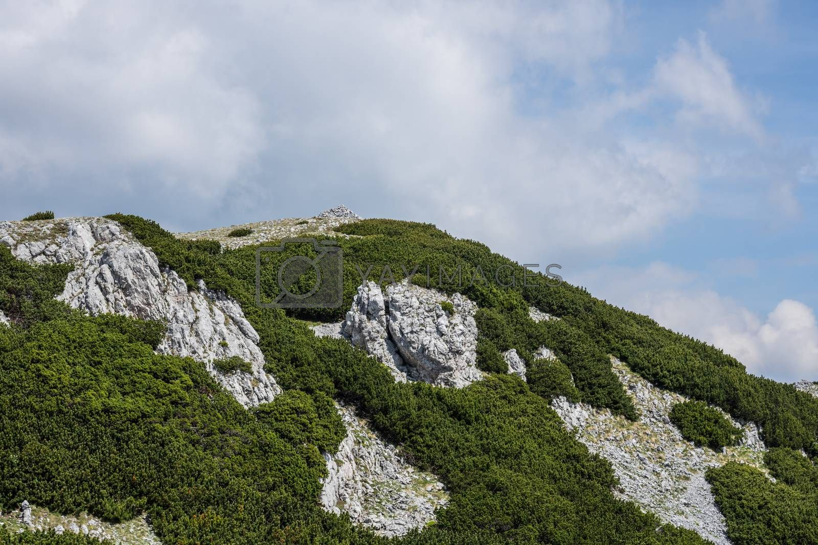 Green mountain with rocks and sky with clouds