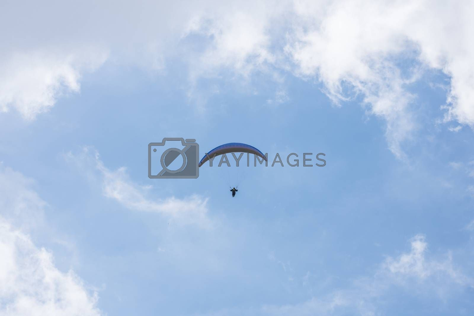Floating paraglider in the blue sky with clouds
