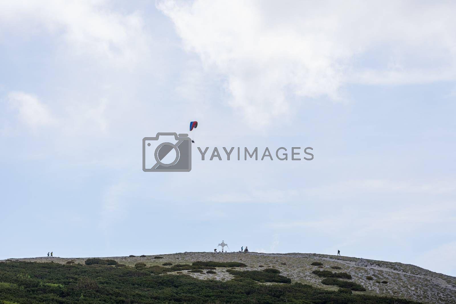 floating paraglider and hiker in the mountains