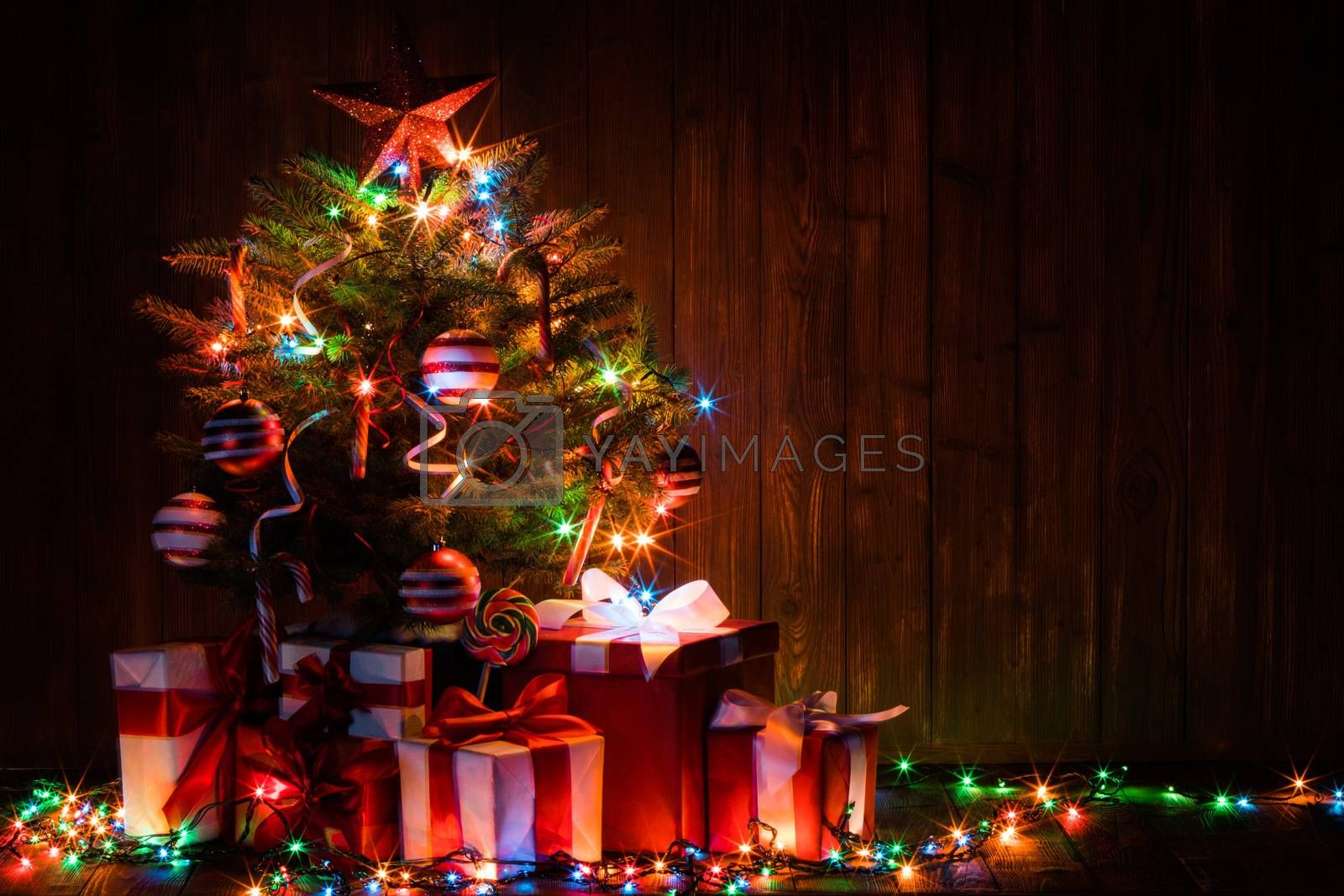 Decorated lighted Christmas tree and gift boxes on wooden background