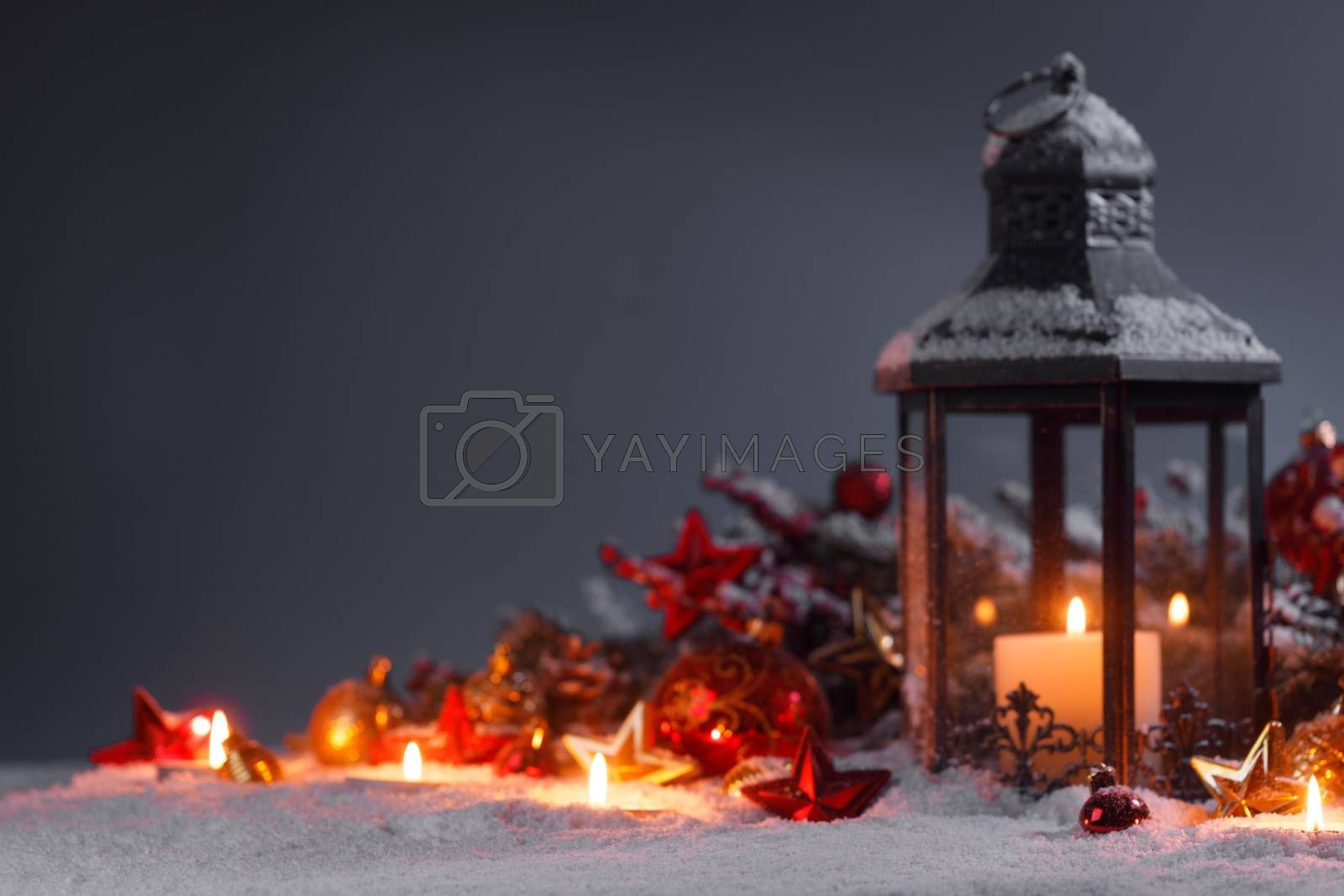 Burning candles , lantern and christmas decoration on snow