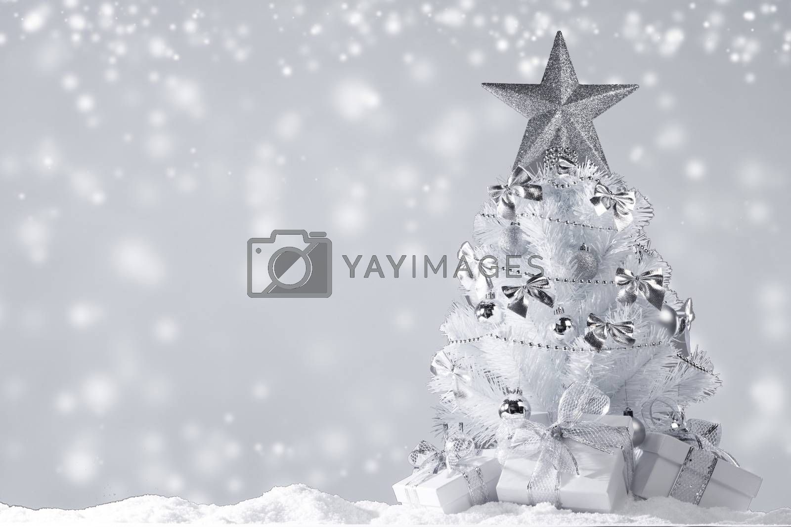 White christmas tree with silver decorations and gifts on snow on magic lights background