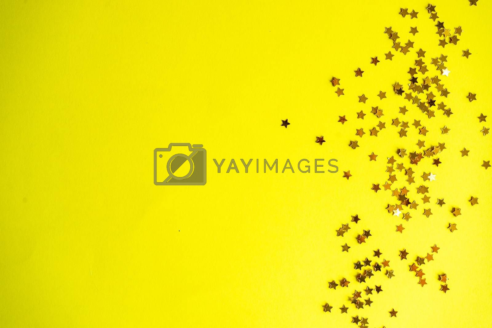 Festive Christmas card concept with star shaped decor on yellow background with copy space