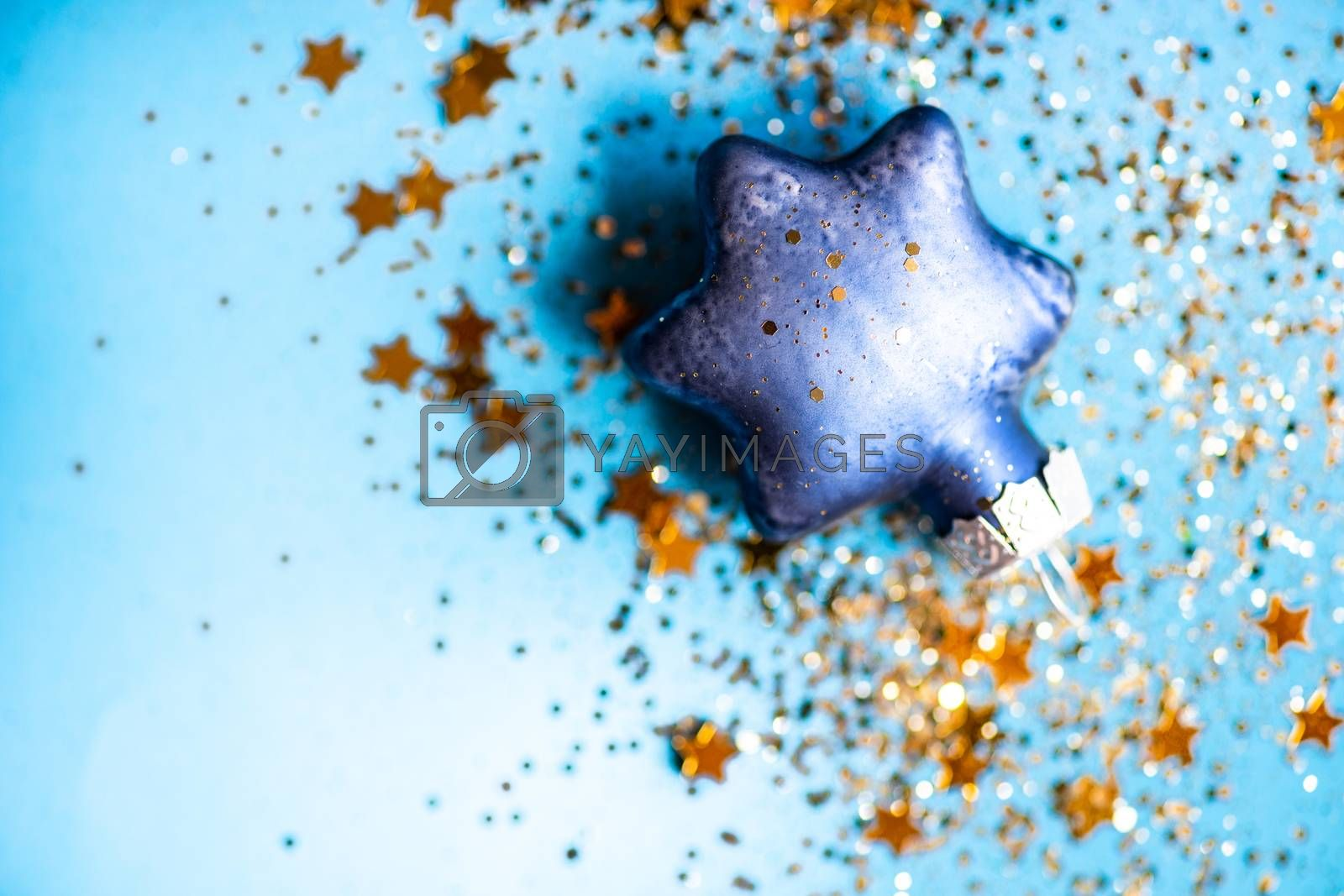 Festive Christmas card concept with star shaped decor on blue background with copy space