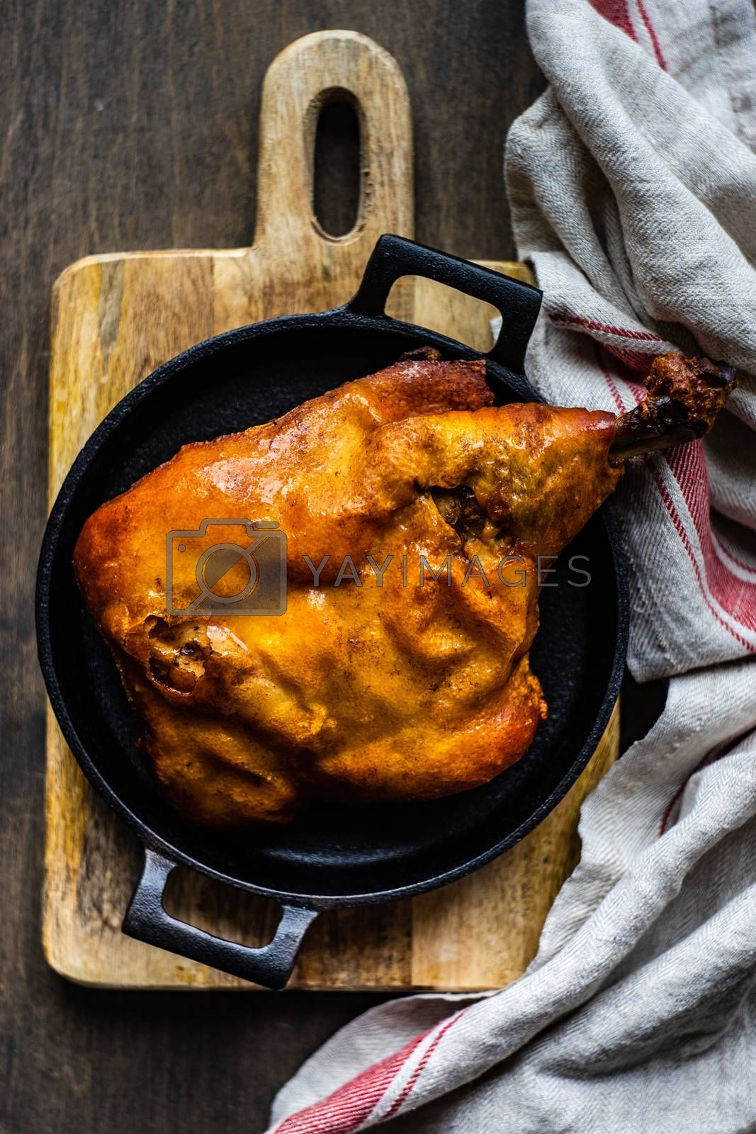 Traditional roasted pork leg in minimal serving on wooden table