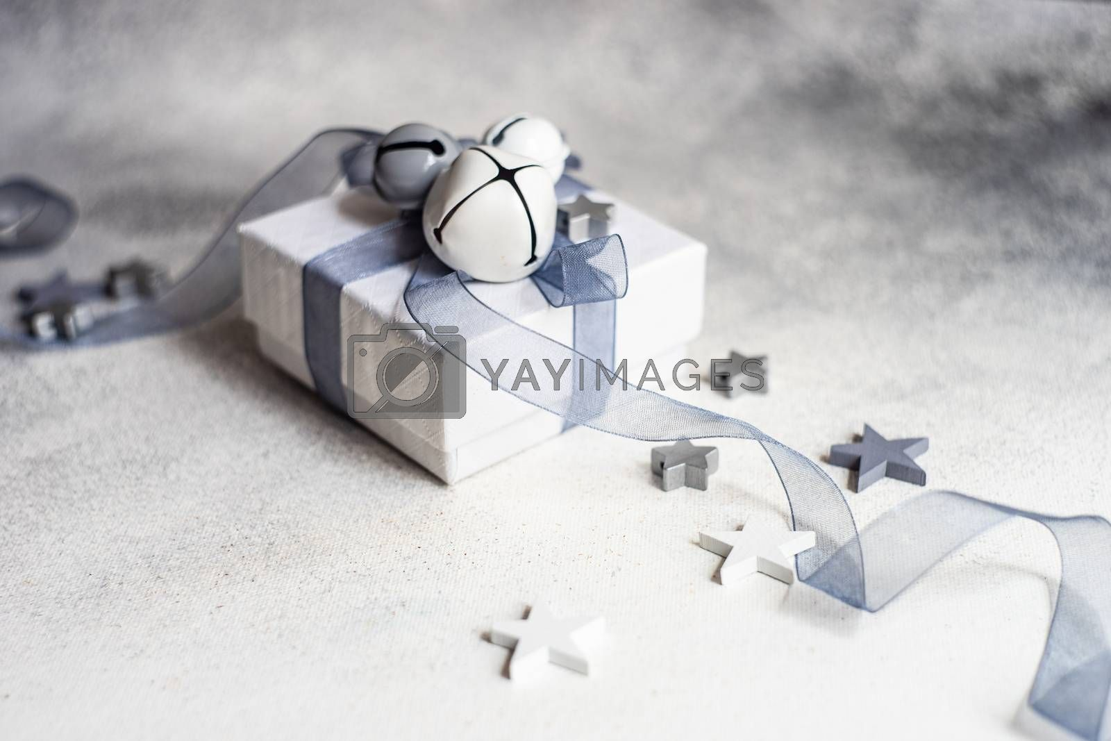 Festive Christmas card concept with gift box and star shaped decor in grey monochrome on concrete background with copy space