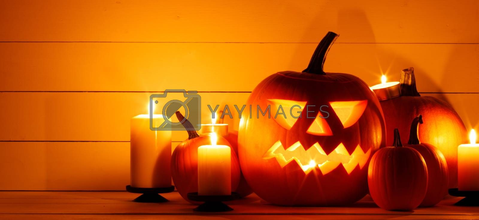Halloween pumpkin head lantern and burning candles orange holiday background