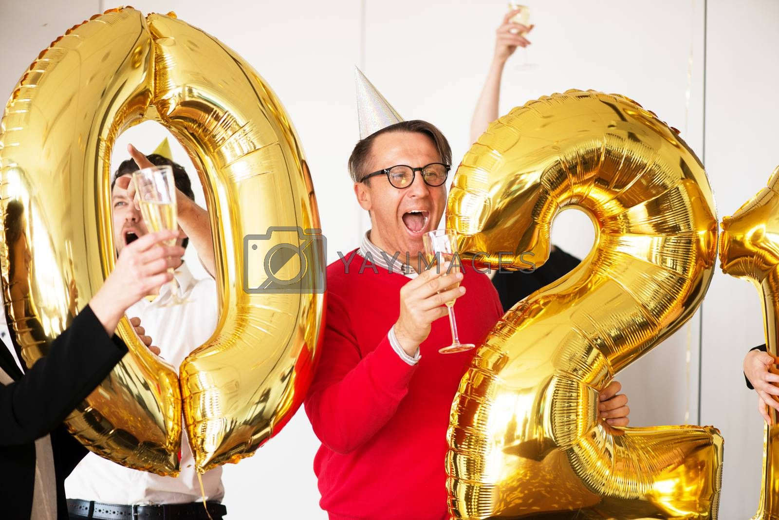 Business people are celebrating holiday in modern office drinking champagne and having fun in coworking. Merry Christmas and Happy New Year 2021. Balloon numbers