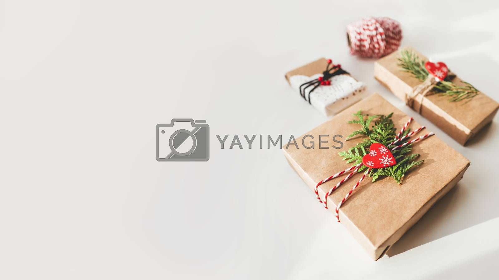 Christmas DIY presents wrapped in craft paper with fir tree branches and red hearts. Decorations on New Year gifts. Festive background. Winter holiday spirit. Banner with copy space.